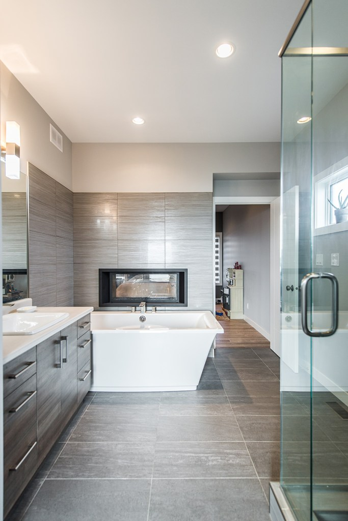 Modern Bathroom with large tiles, vanity with vinyl doors and white quartz countertop, contemporary bathtub and shower, and fireplace