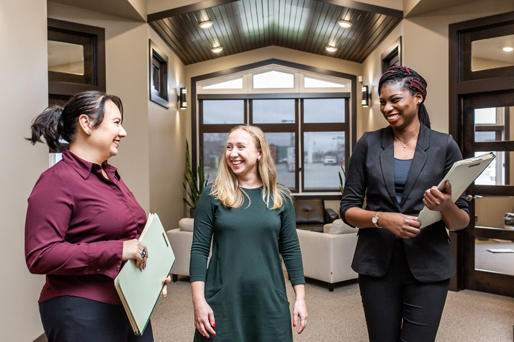3 business women standing in brand new home/living room area, laughing and holding files