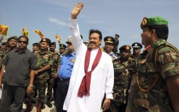 Sri Lankan President Mahinda Rajapaksa waves during a photo opportunity with high-ranking military officials after unveiling a monument for fallen Sri Lankan soldiers in the town of Puthukkudiriruppu, December 9, 2009. REUTERS/Lakruwan Wanniarachchi/Pool (SRI LANKA POLITICS CONFLICT ELECTIONS MILITARY)