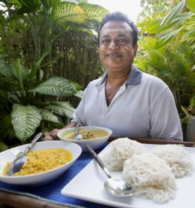 Carman Abeyeunga, a member of the staff, serves string hopper, fish curry and yellow dal