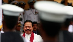 Rajapaksa smiles as he looks at Sri Lankan Navy sailors standing at attention during ceremonies to celebrate the Navy's 60th anniversary in Colombo