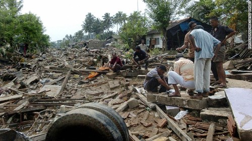 Sri Lankan men sort through debris of their destroyed homes in Galle on December 27, 2004.