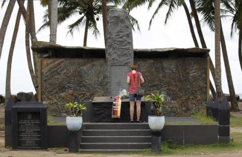 Tourist stands in front of the Tsunami memorial in Pereliya