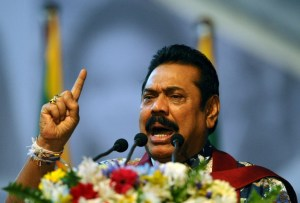 Sri Lankan President Mahinda Rajapakse addresses to supporters as he attends an election rally in the Colombo suburb of Piliyandala on January 5, 2015. Gunmen shot and wounded three opposition activists who were preparing a stage for President Mahinda Rajapakse's chief rival on the final day of campaigning in Sri Lanka's election, police said. The men were hit in a drive-by shooting as they erected a podium for Maithripala Sirisena to address a rally in the southern town of Kahawatte, around 130 kilometres (80 miles) from the capital Colombo. AFP PHOTO / LAKRUWAN WANNIARACHCHI