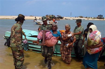 In this photograph released by the Sri Lankan navy April 22, 2009, members of the military assist from a boat some of the thousands of people that fled an area called the 'No Fire Zone' controlled by the Liberation Tigers of Tamil Eelam (LTTE), in northern Sri Lanka. REUTERS/Sri Lankan Government/Handout