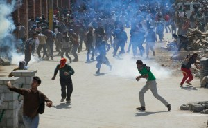 Kashmiri protesters throw stones and bricks at Indian policemen during a protest in Srinagar, Indian controlled Kashmir, Friday, April 17, 2015. Police fired tear gas and rubber bullets Friday to disperse hundreds of demonstrators in Indian-controlled Kashmir who hurled rocks and chanted anti-Indian and pro-Pakistan slogans to protest the killing of a militant commander's brother. The Indian army said the man was killed in a gunbattle along with a militant on Monday, while his relatives and local residents said he was tortured to death. (AP Photo/Dar Yasin)