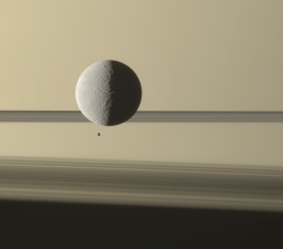 Two of Saturn's moons meeting, seen against the ghostly shadow of the rings