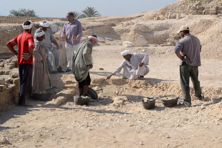 Obreros excavando donde ha sido hallado el pozo de tumba en el yacimiento.