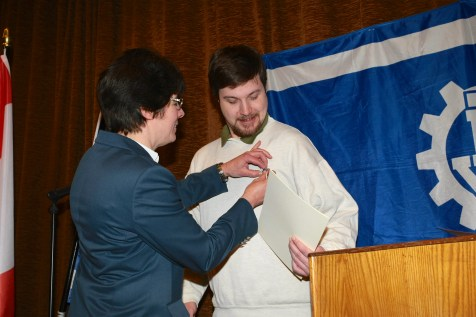 Hedwig Karkut ehrt Jonas Sellin mit dem Helferzeichen in Gold.
