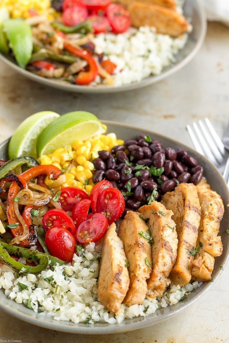15-Minute Chicken Fajita Cauliflower Rice Bowls - bowl of cilantro lime cauliflower rice topped with grilled chicken, black beans, corn, grilled onions and peppers plus fresh tomatoes