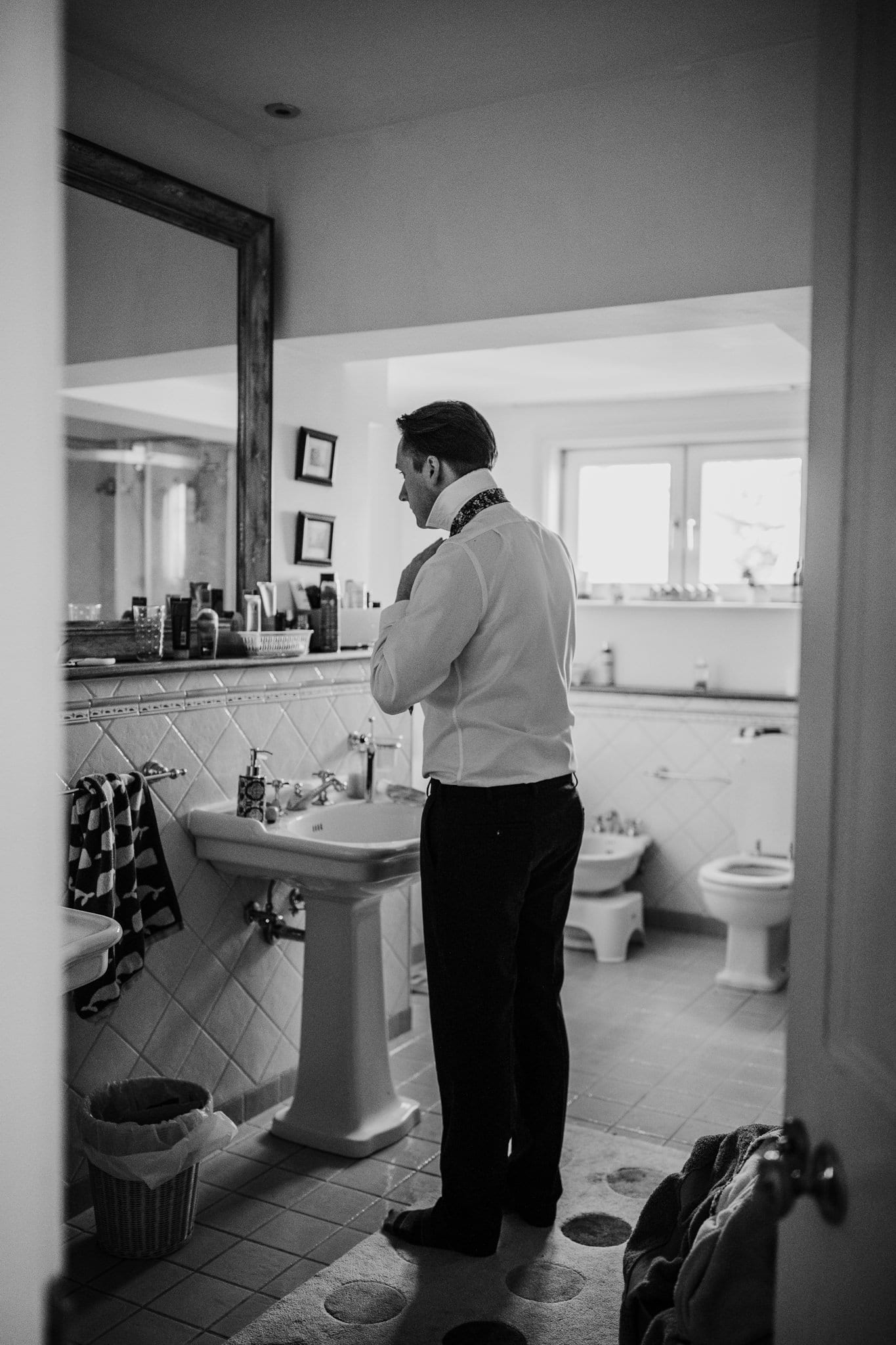 man adjusting his tie in the bathroom
