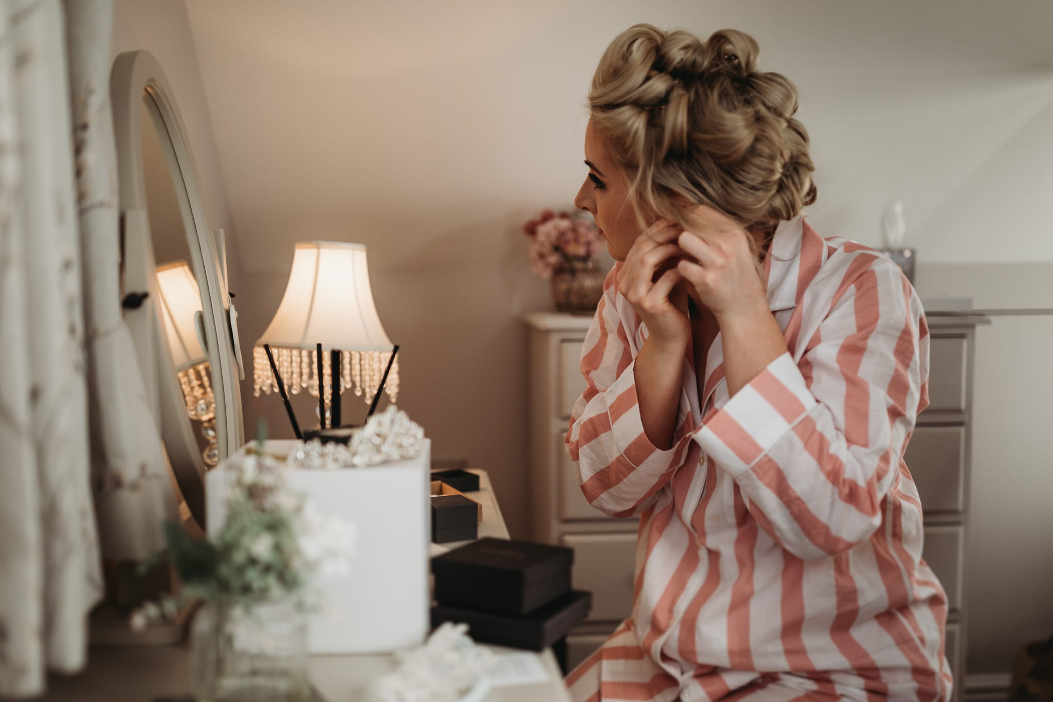woman putting earrings on in front of a mirror