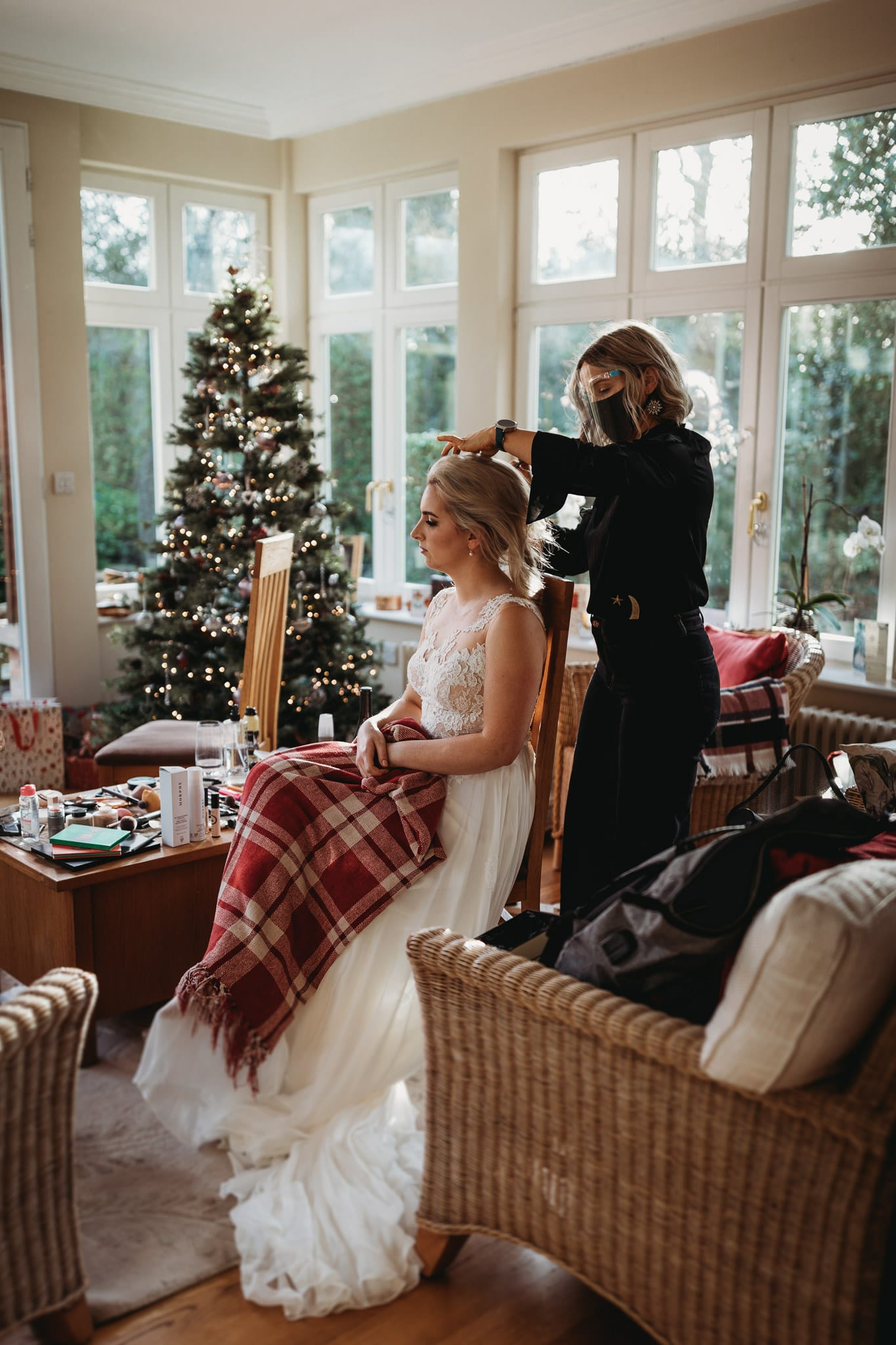 bride having her hair done in front of a christmas tree, holding a chequered blanket on her lap