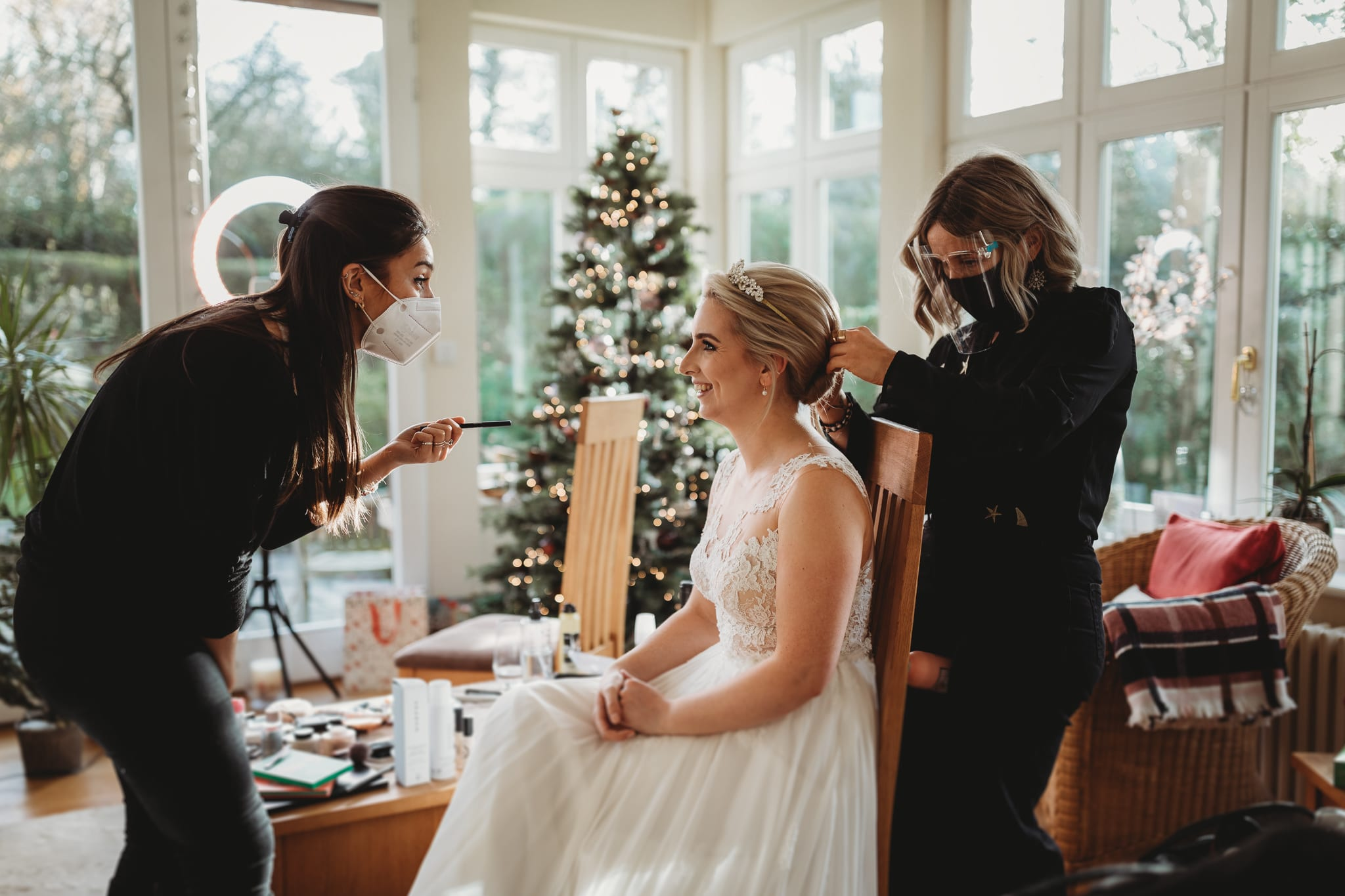 bride having hair done and makeup applied in front of a christmas tree