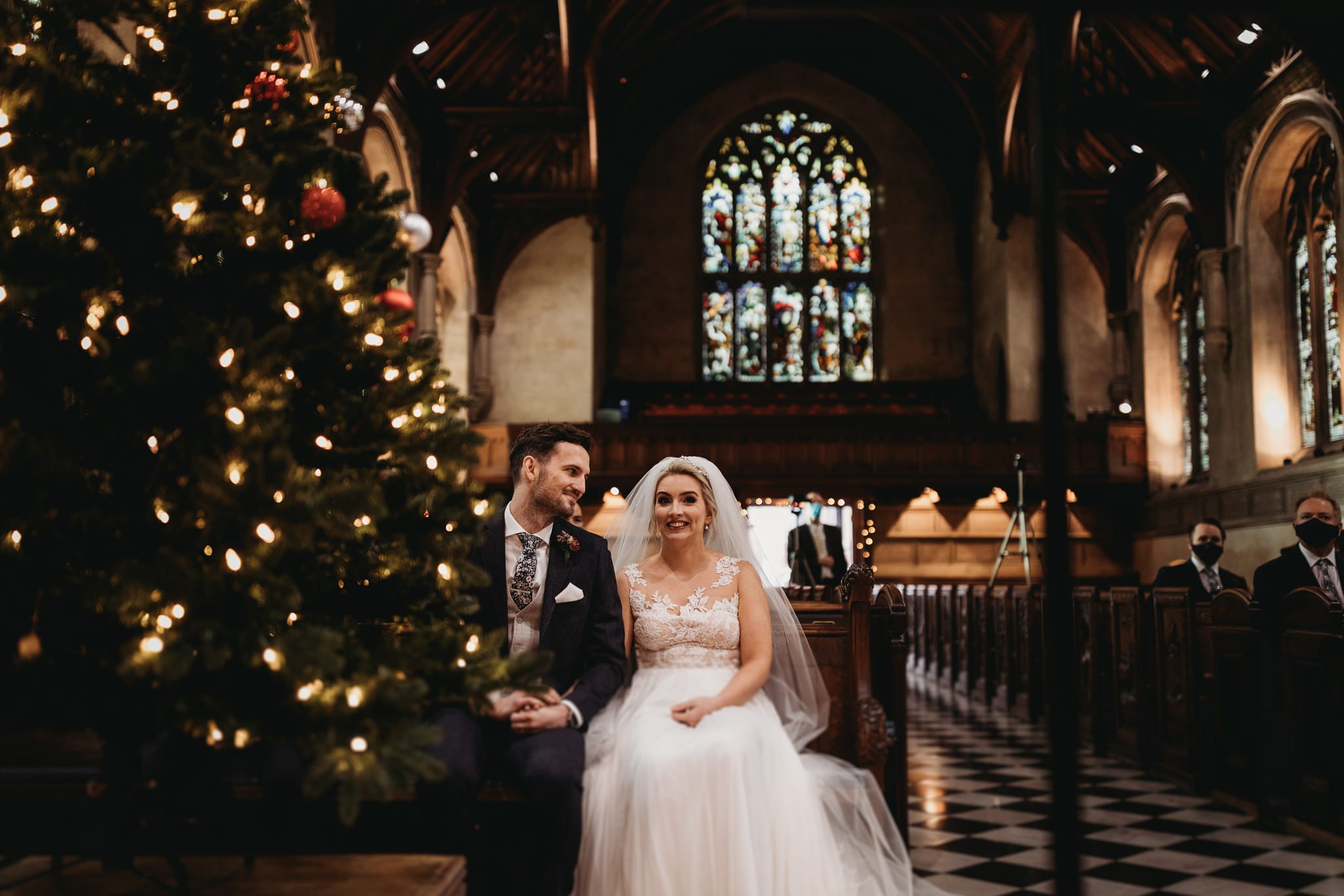 bride and groom sitting in front row in the church, Christmas tree in front