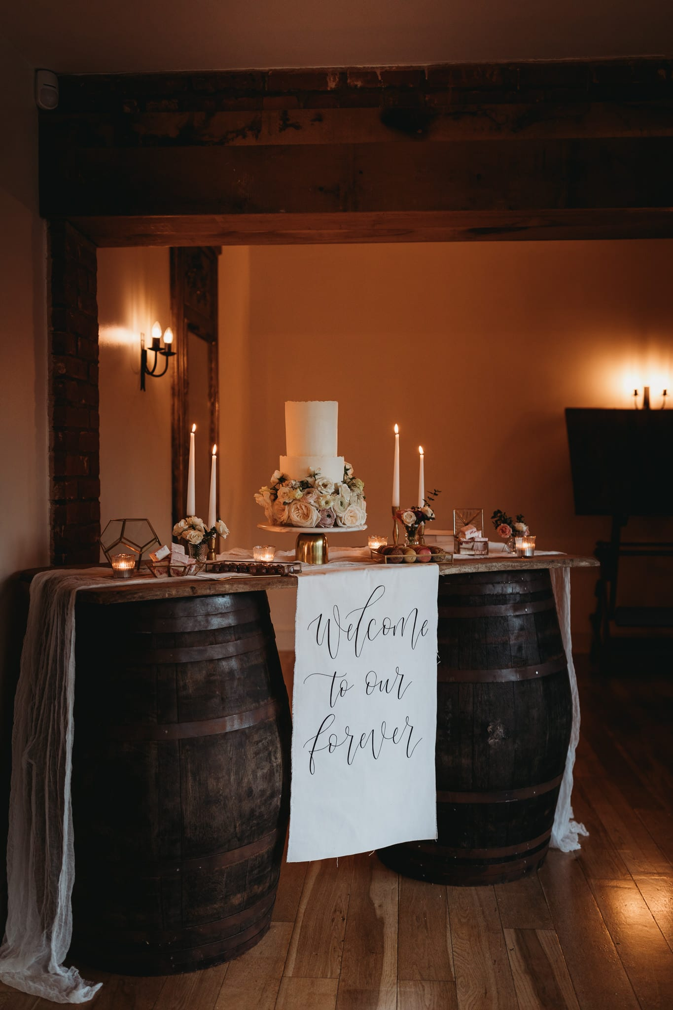 cake table setup with warm lights in background at Granary estates intimate wedding