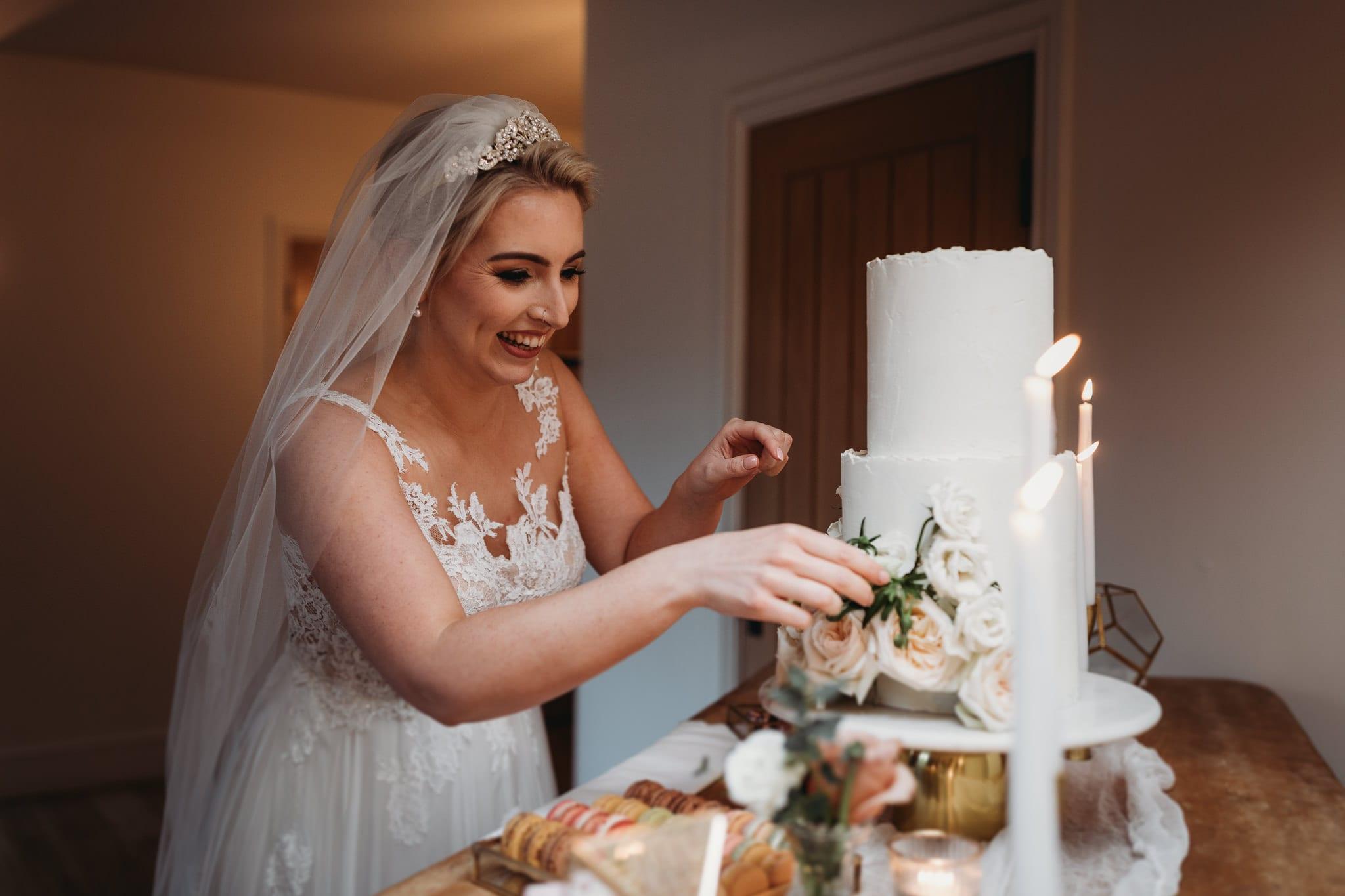bride adjusting flowers on the cake at Granary Estates Intimate wedding