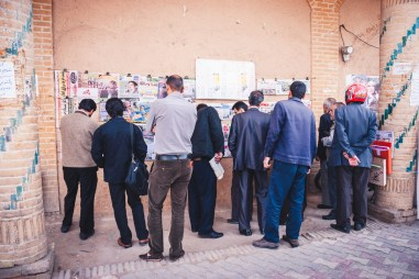 Men reading the news on a wall in Yazd