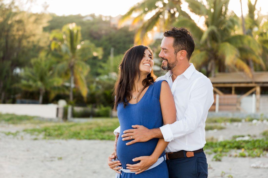 Couple souriant durant une séance grossesse sur une plage à la Réunion