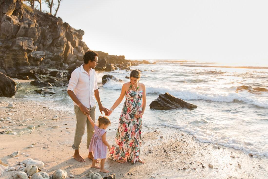 Une famille qui marche sur le sable d'une plage de la réunion au coucher du soleil Futurs parents immortalisés par une photographe de grossesse professionnelle