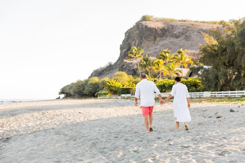 Un couple de grands-parents qui marche sur une plage de la Réunion