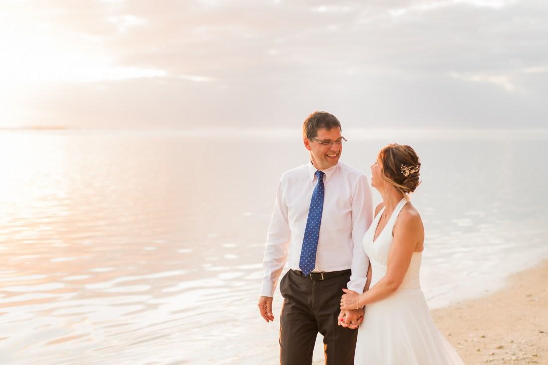 Un couple heureux qui marche sur la plage après leur renouvellement de voeux de mariage