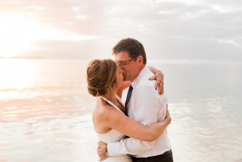 Un couple qui s'embrasse sur la plage lors de leur renouvellement de voeux de mariage