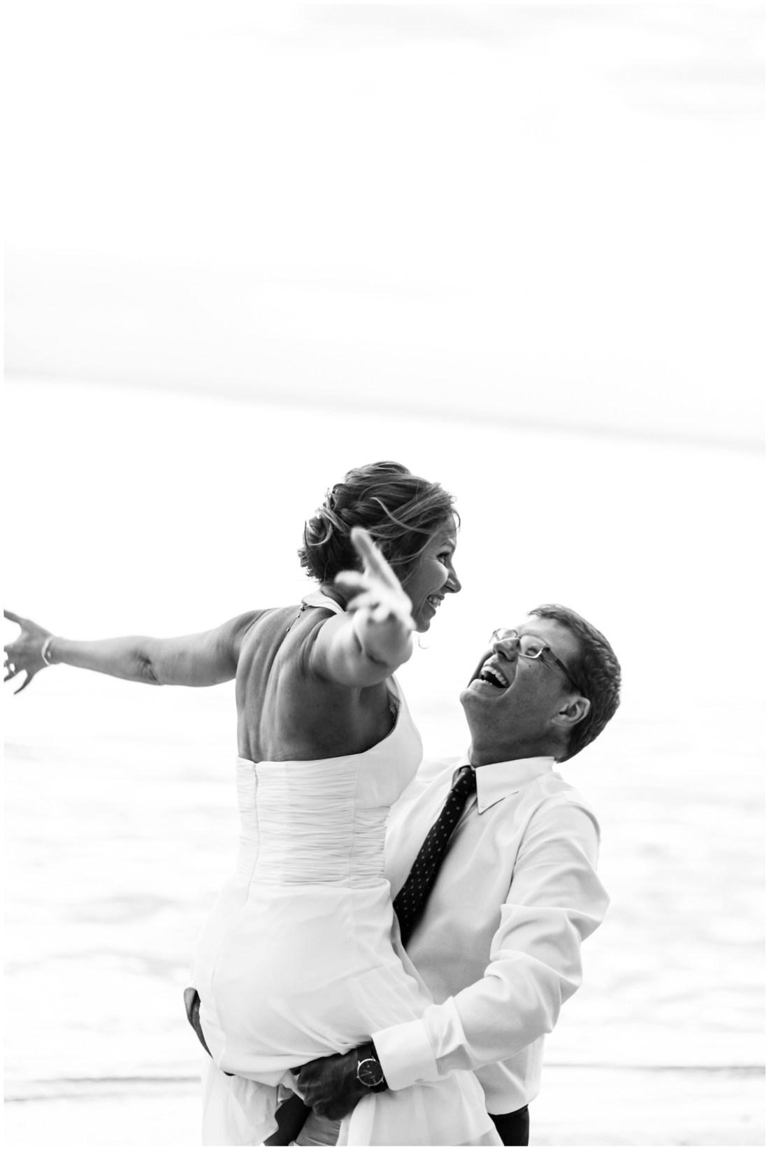 Un couple fun qui s'amuse sur la plage lors de leur renouvellement de voeux de mariage