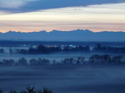 View of the Pyrenees silhouetted against a streaky muted orange skye, looking over early morning mist amid dark lines of trees and the lights of a distant town in the Adour Valley