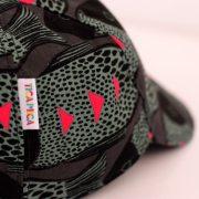 Gorra con visera y cierre con velcro. Estampado en negro y gris y detalles en fucsia
