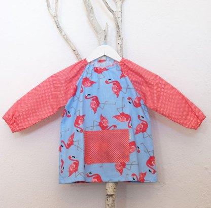 Bata infantil para guardería con estampado de flamencos y mangas y bolsillo con lunares en rosa.