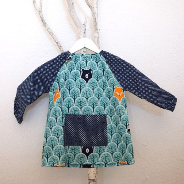 Bata para guardería con estampado turquesa con zorros, combinado en mangas y bolsillo en azul oscuro.