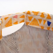 Detalle de la gorra con visera en amarillo, blanco y azul