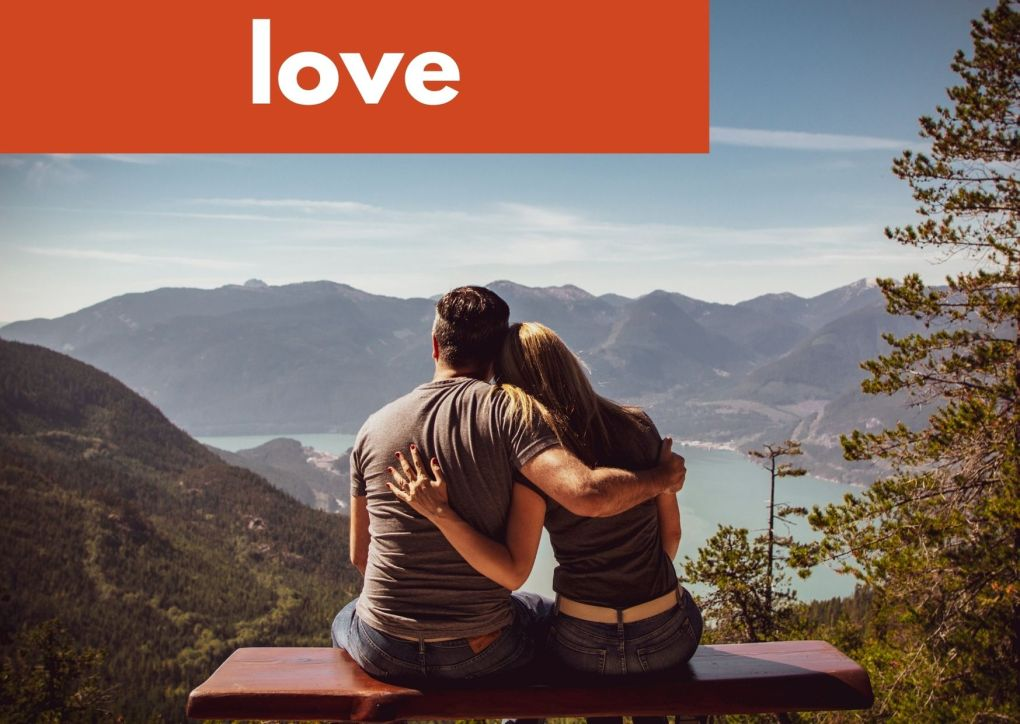 a couple sitting on a bench with arms around each other looking at a mountain view and the word love