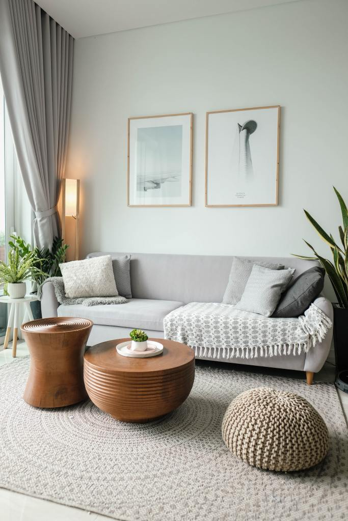 grey sofa with cream colour throw and pillows, organic circular coffee tables, large plants, Scandinavian style photo