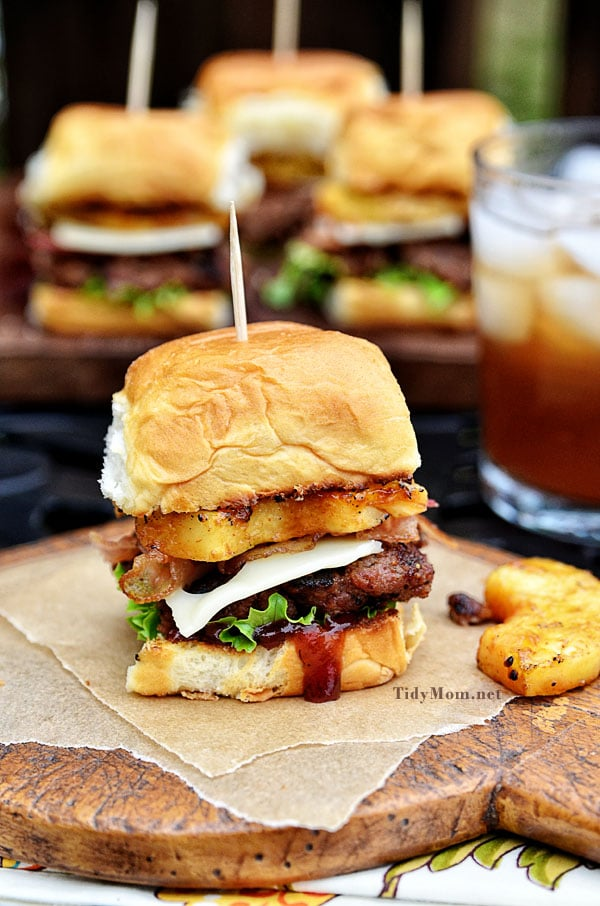 Fire up the grill for this Hawaiian burger recipe. Aloha BBQ Sliders are flavored with BBQ sauce, served on sweet rolls with cheese, pineapple and bacon. Print recipe at TidyMom.net