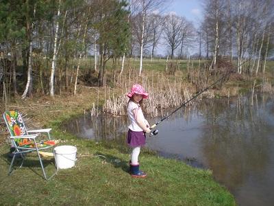 """Der Nachwuchs """"Amy"""" angelt am Teich auf Karpfen."""