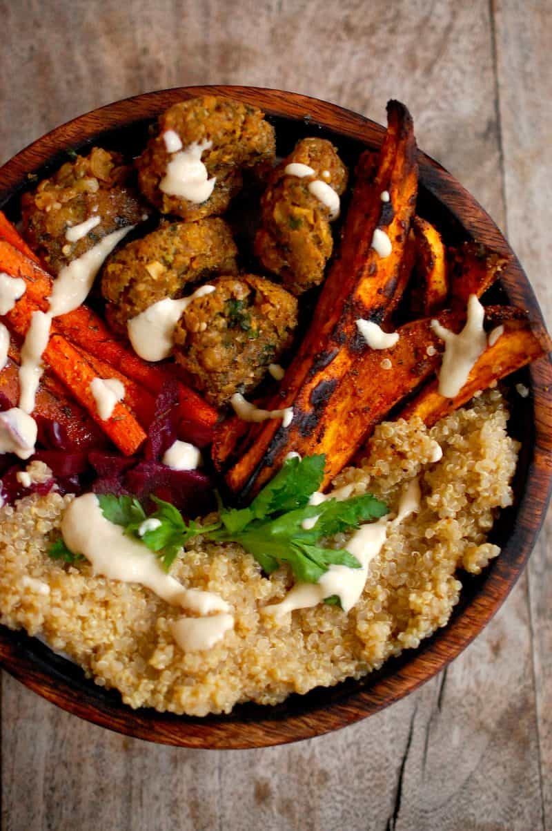 Falafel with a tahini sauce, sweet potato fries, roast carrots and Quinoa in wooden bowl on table