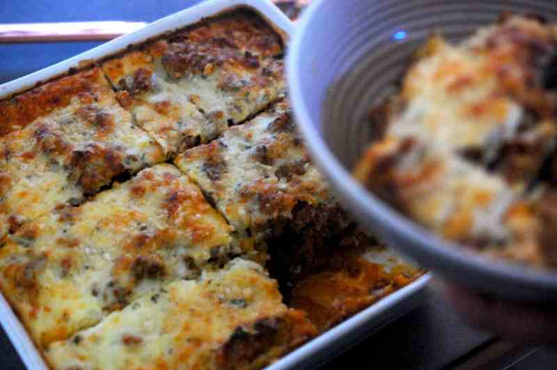 Moussaka cut into slices in baking dish with one slice in bowl