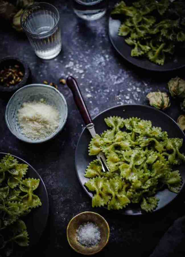 3 plates of pesto pasta with toppings