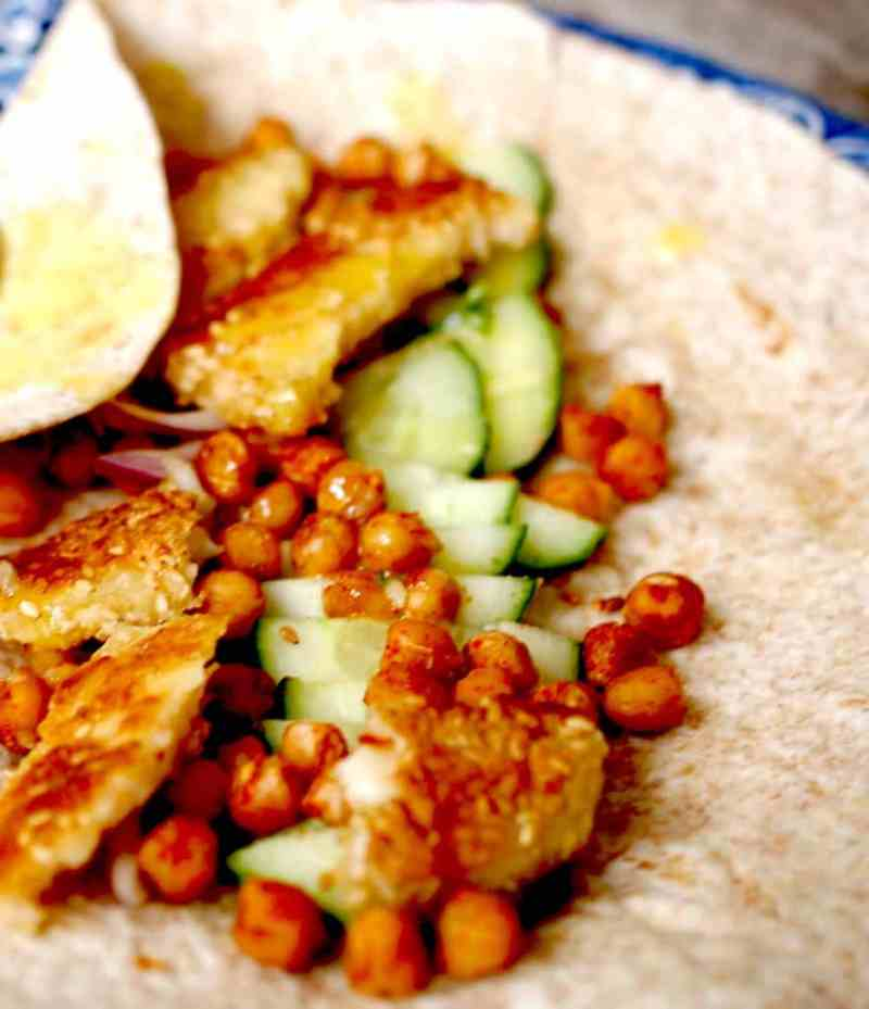 Chickpea, sweet potato and Halloumi wrap laid open on blue plate