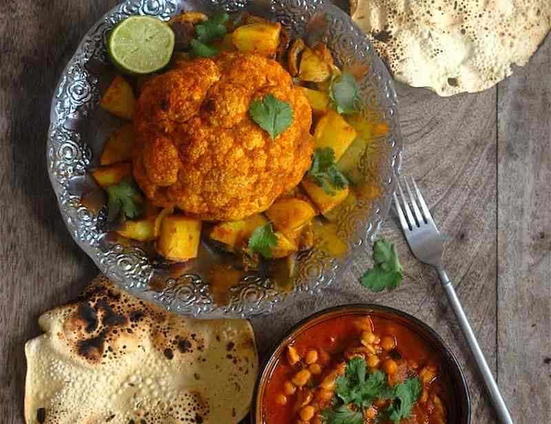 Chicken and chickpea curry on table with popadoms and whole roast cauliflower