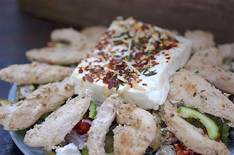 Feta and chicken on a bed of salad on a plate