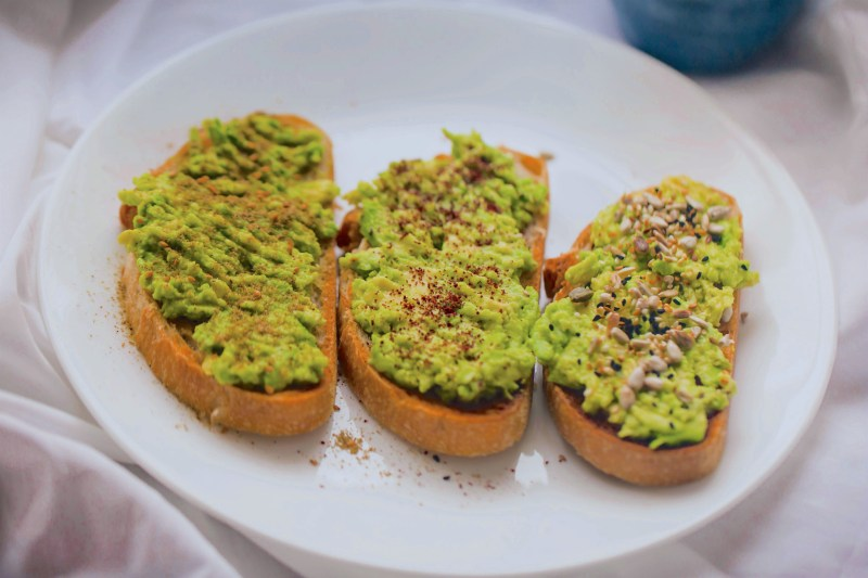 3 smashed avocado on toast on a white plate