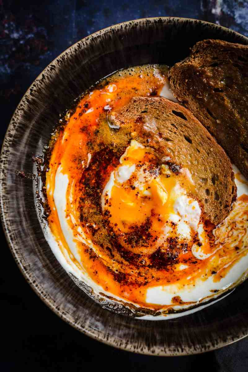 Cilbir with 2 toast in dark bowl