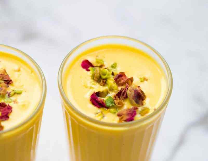 Mango lassi drink in two drinking glasses