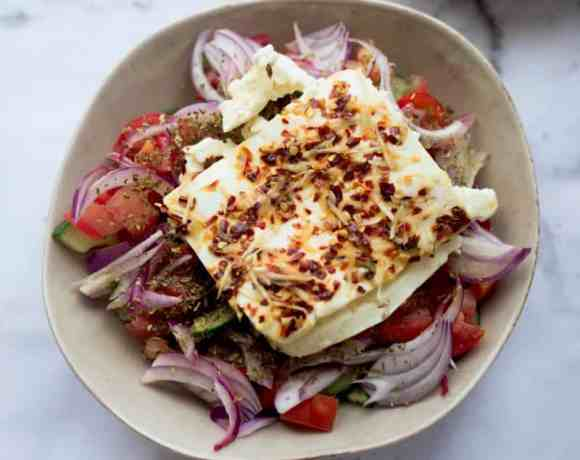 Greek Salad with feta in a bowl on marble background