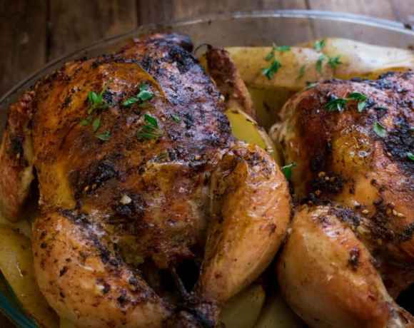Full roast chicken with potato wedges in casserole dish on wooden table