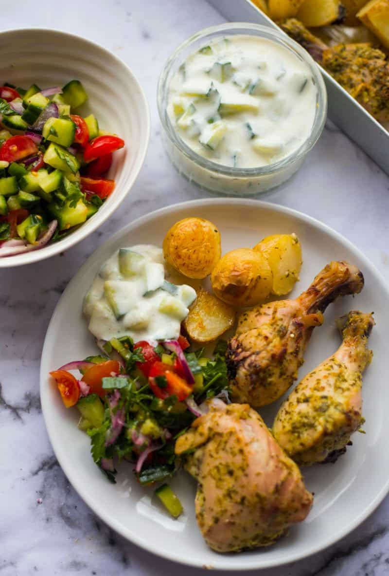 Greek chicken in a plate with potatoes and salad