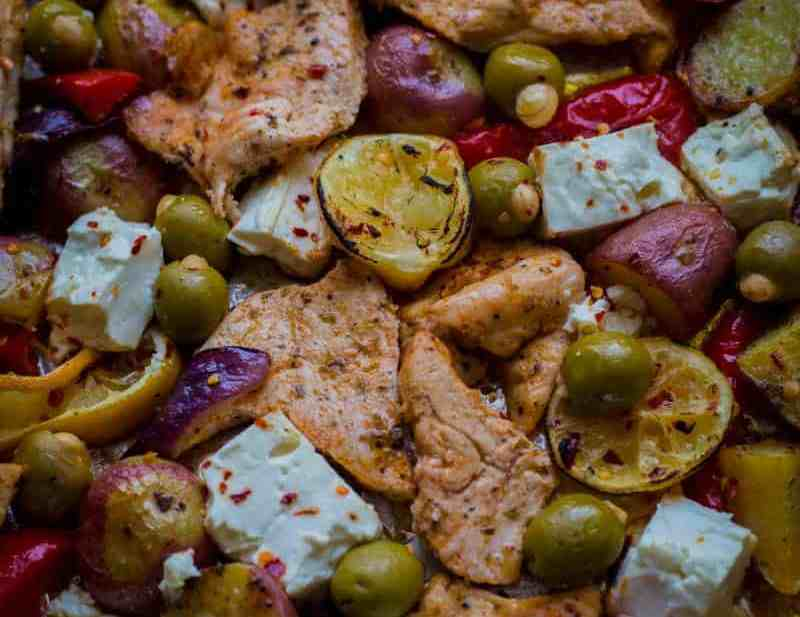 Mediterranean Chicken Tray Bake with Potatoes, Olives, Pepper and Feta spread out in tray